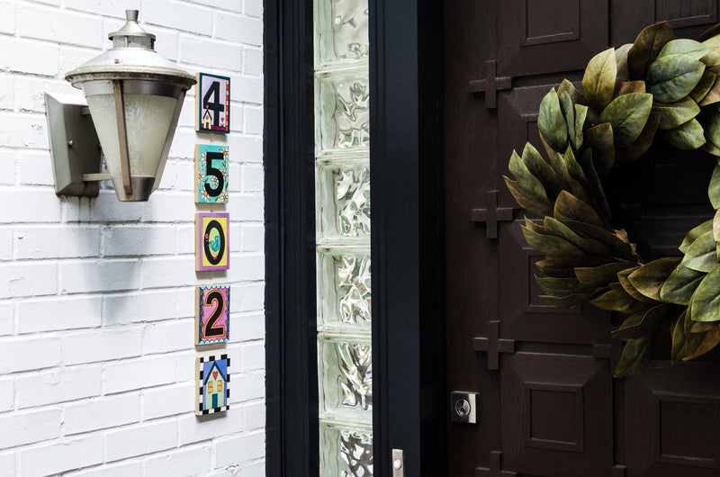 Sincerely, Sticks printed number plaques displayed by a front door