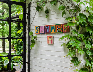 Sincerely, Sticks alphabet plaques spelling out Summer on a patio