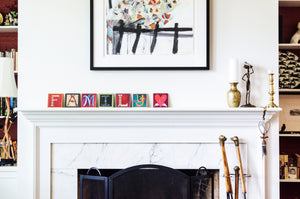 Example of Sincerely, Sticks alphabet letter plaque spelling out Family on a fireplace mantle