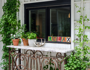 "Example of Sincerely, Sticks ""X"" alphabet letter plaque to spell out Relax on a window sill"