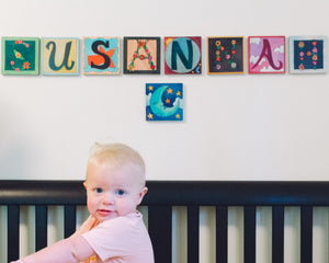 Example of Sincerely, Sticks alphabet letter plaques spelling Susannah over a crib