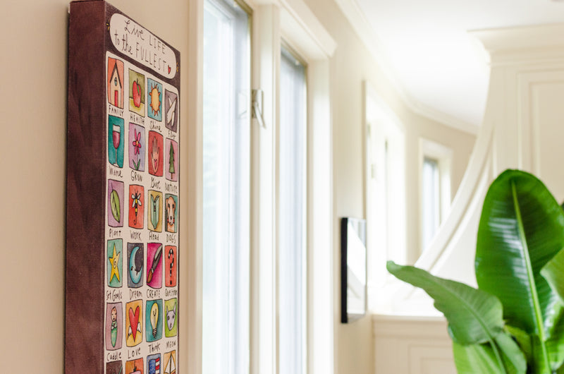 "Sincerely, Sticks printed stretched canvas wall art with colorful and symbolic block icons, ""Live Life to the Fullest"", staged on a home's wall"