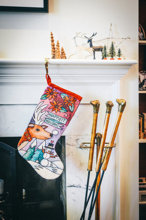 """Happiest Holiday"" Canvas Stocking – Rudolph wishes you the ""happiest holidays"" in a winter wonderland design displayed on a fireplace mantel"