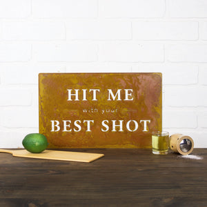 "Hit Me with Your Best Shot Wall Plaque – This witty metal sign that reads ""Hit me with your best shot"" and we see it being the perfect addition to any kitchen or bar area"