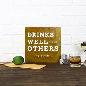 "Drinks Well With Others Wall Plaque – Square metal sign with phrase ""Drinks well with others"" would make a perfect addition to a kitchen or bar area in you home or to gift to a drinking buddy"
