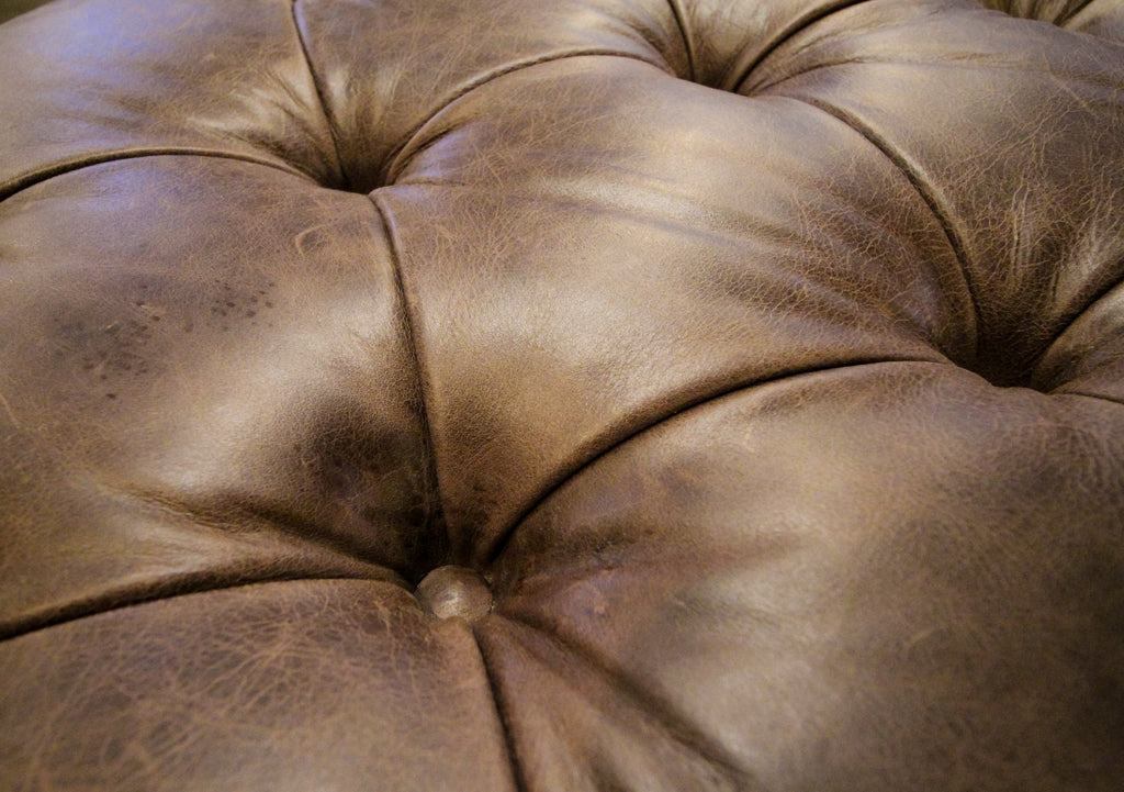 Hand tufted diamond button tufting on top of leather ottoman