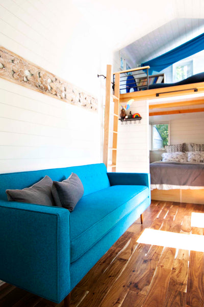 The teal blue Sterling custom sofa from Perch Furniture provides a comfortable place to lounge at the center of this tiny home