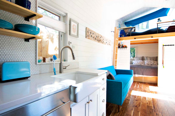 Teal accents create a pop of color in this modern farm house style tiny home on wheels.