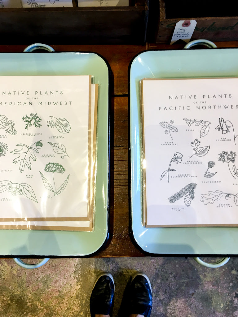 Letter Press cards sit on vintage enamel trays in a display at the boutique Porch Light in Portland, Oregon.