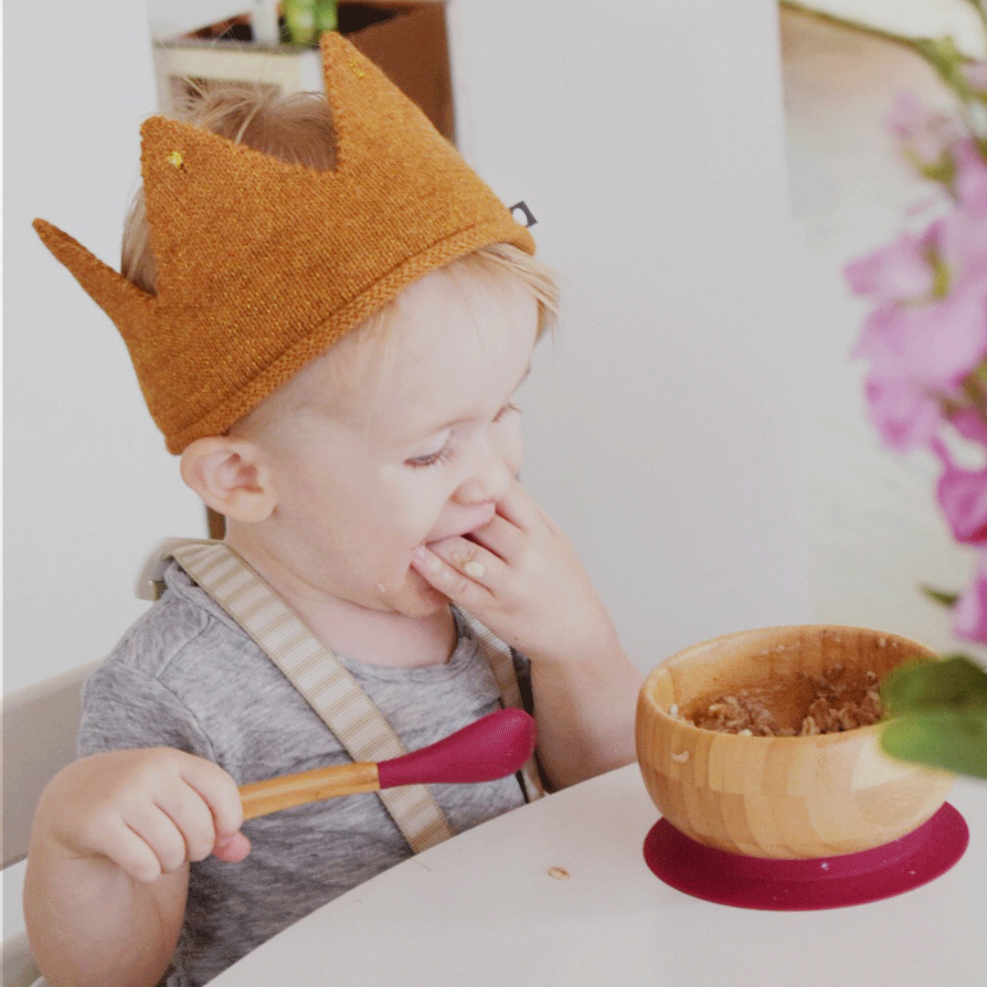a little boy sitting in a high chair eating from a wooden bowl and spoon wearing a orange felt crown