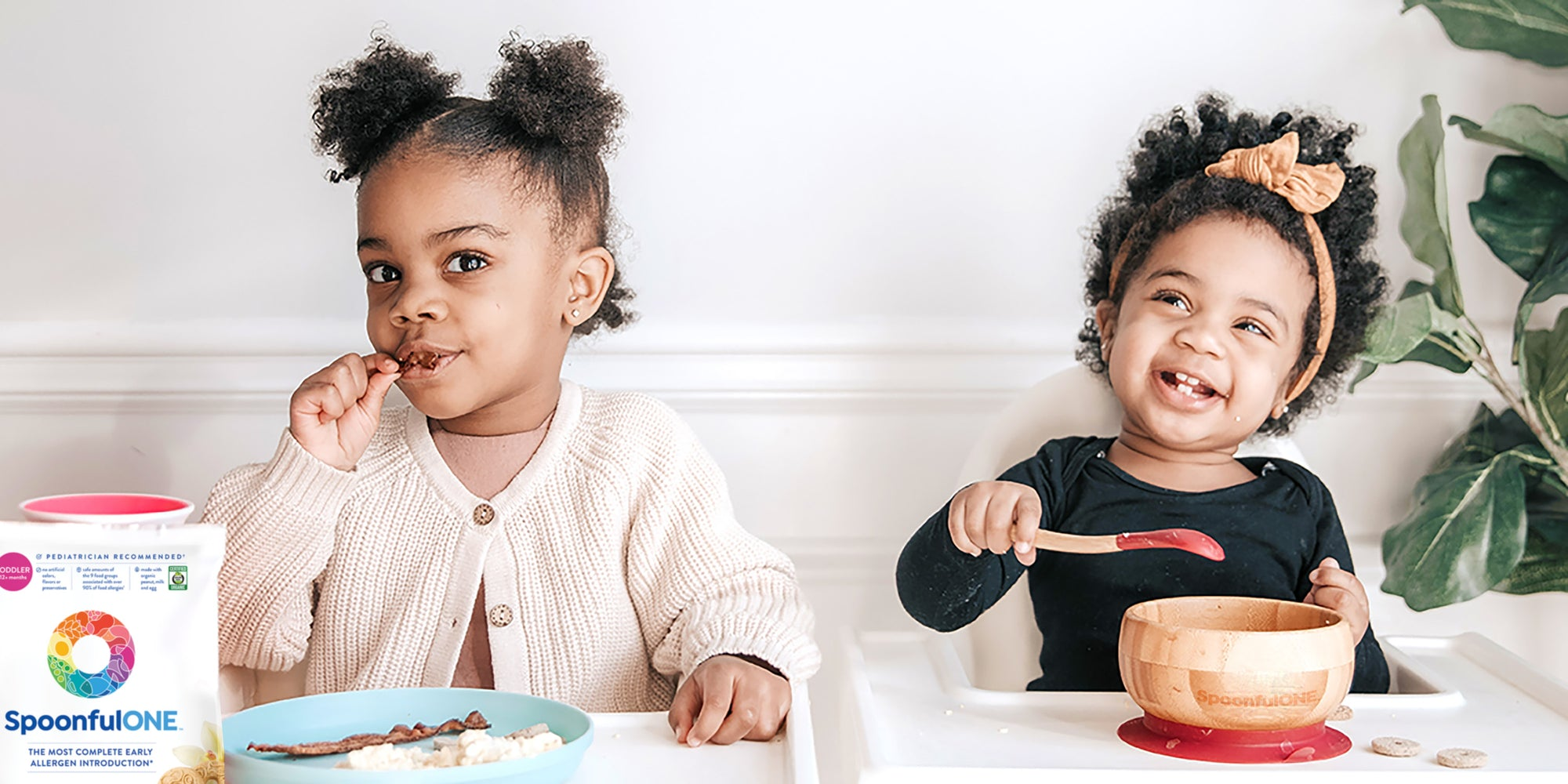 two little girls eating spoonfulone oatcrackers and mixins