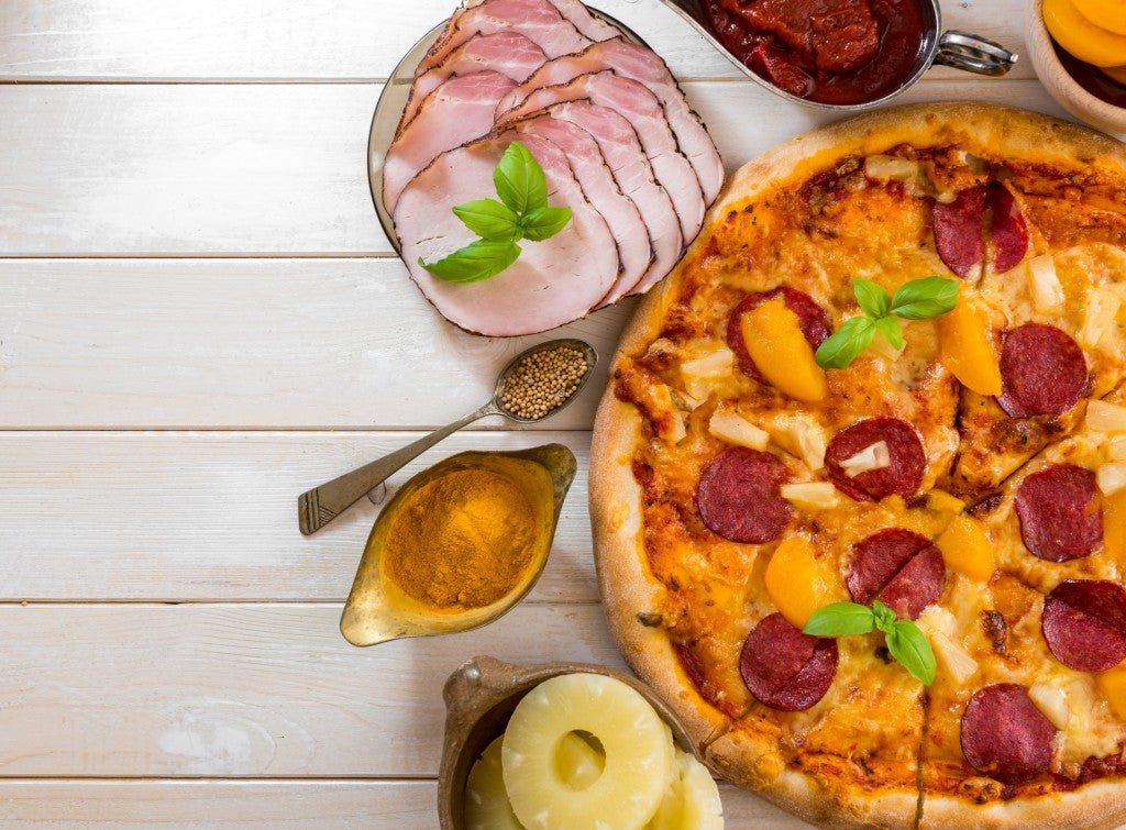 exotic pizza with pineapple and peach with food ingredients on a wooden table