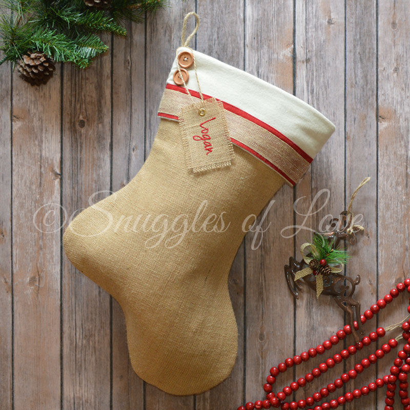 Six burlap stockings with red and cream details and hanging tags