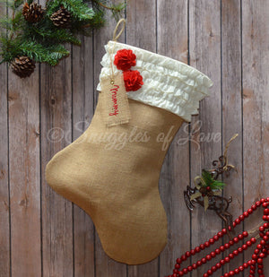 Cream ruffled burlap Christmas stocking with red burlap flowers and embroidered name tag