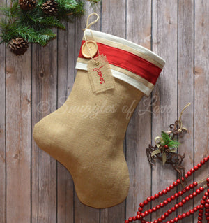 Burlap Christmas stocking with red cuff detail, wood button and embroidered tag