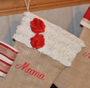Tan burlap stocking with cream ruffles on stocking cuff and two red burlap flowers