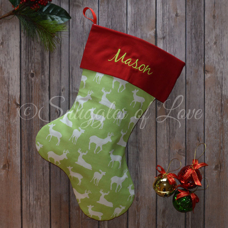 Embroidered Christmas stocking with green deer fabric and red cuff