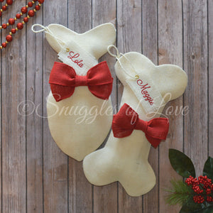 Ivory burlap dog and cat stockings with red bows and hanging tags