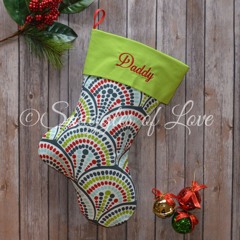 Personalized blue Christmas stocking with blue, red and green arc pattern
