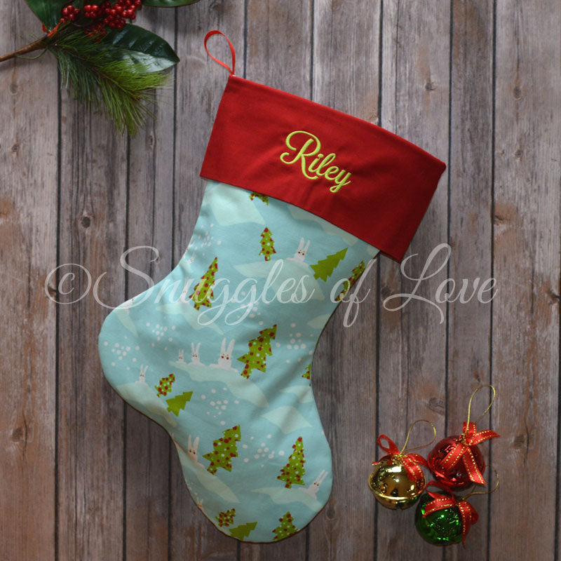 Blue Christmas stockings with bunnies, snow and Christmas trees