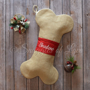 Tan burlap dog bone Christmas stocking with red embroidered middle band