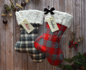 Two plaid flannel Christmas stockings with fur cuffs and monogrammed name tags