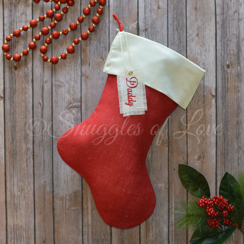 Red burlap Christmas stocking with cream satin cuff and personalized name hanging tag