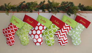 Six coordinating red and green patterned personalized Christmas stockings