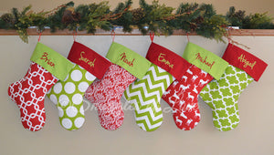 Six red and green Christmas stockings with embroidered names