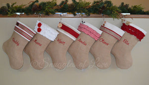 Six coordinating personalized burlap Christmas stockings in red and cream colors