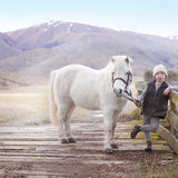 boy enjoying the outdoors with his white pony