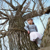 girl atop a tree in merino top and leggings