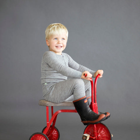 young boy in grey merino top and leggings riding a bike