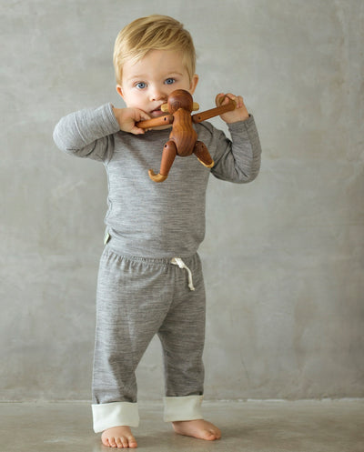 baby wearing grey long sleeve top and drawstring pants