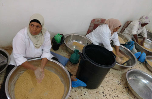 Women sitting and sifting Maftoul