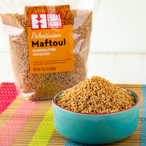 Bowl of Palestinian Maftoul couscous in front of a bag of the same