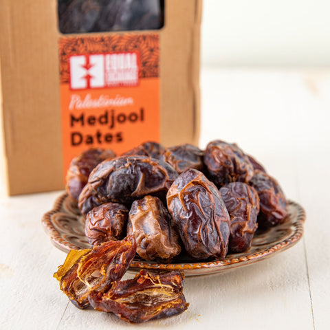 Bowl of Palestinian Medjool Dates in front of a box of the same