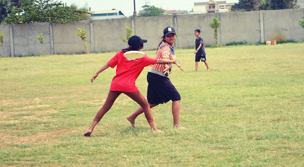 Girl breaks opponents force with a backhand throw during a game of ultimate at an ultimate frisbee camp in Cambodia