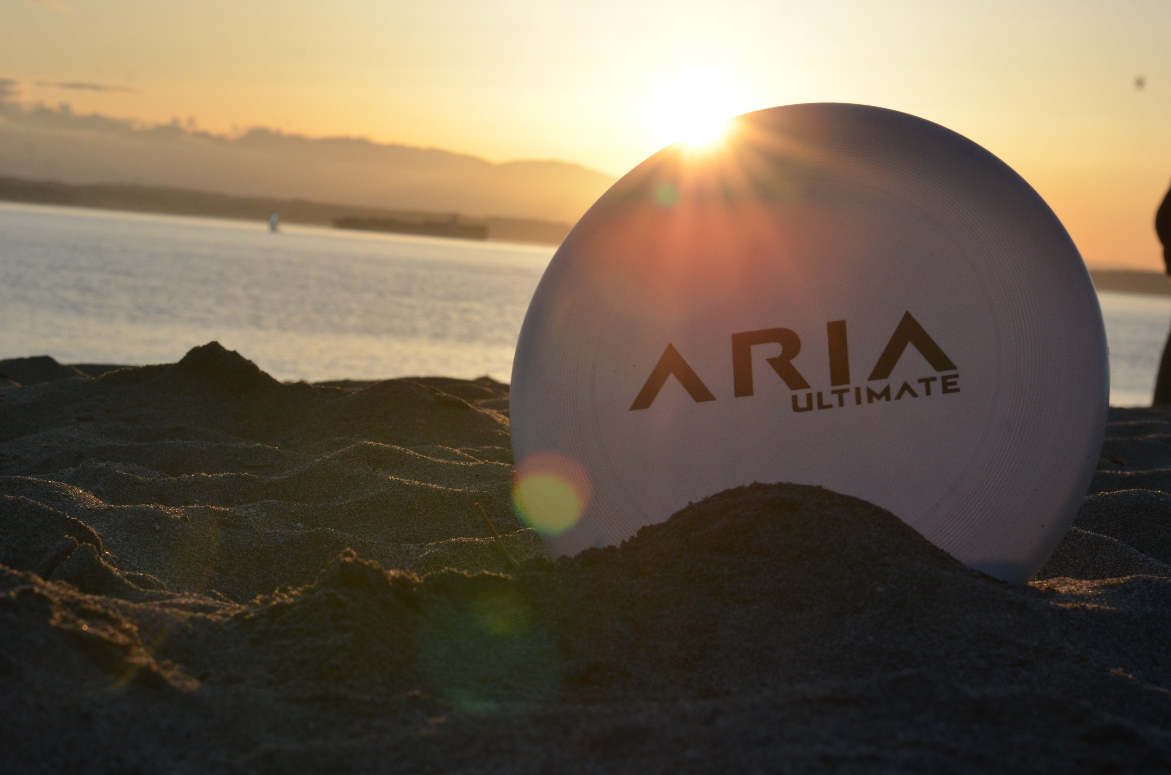 An ARIA Ultimate disc on the beach at sunset.