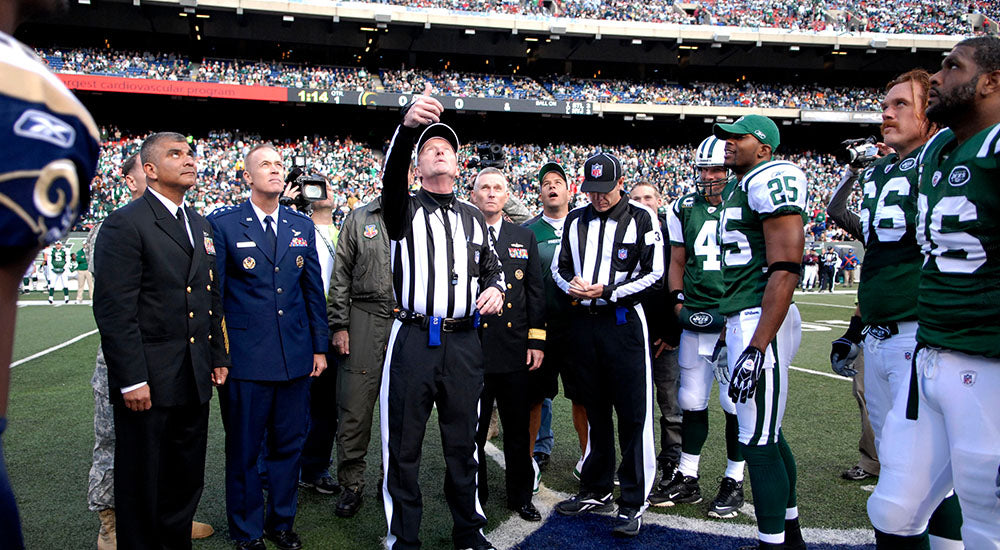 A large group of men watch and participate in the coin toss at a National Football League game.