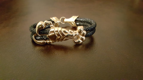 An elegantly handcrafted gold scorpion black exotic stingray bracelet - made of only the most exquisite materials found.