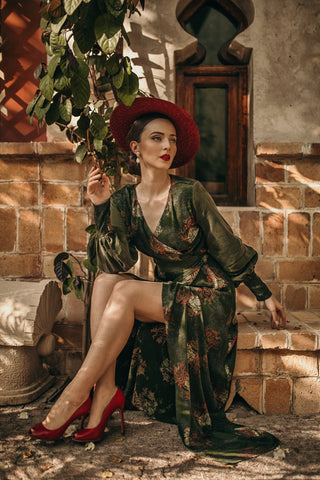 Blogger Aida Đapo Muharemović wearing our iconic green maxi wrap dress, Verdant. Styled with a wide brimmed hat and matching red heels.