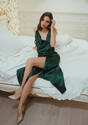 Model is lounging on a white bed in our Emerald Green Slip Maxi Dress Rosie