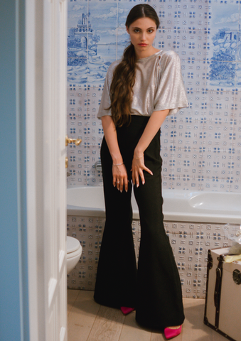 Model wearing our high waist glitter flares, Cobie, with a simple grey t-shirt tucked into them and hot pink stiletto heels poking out from under the hem.