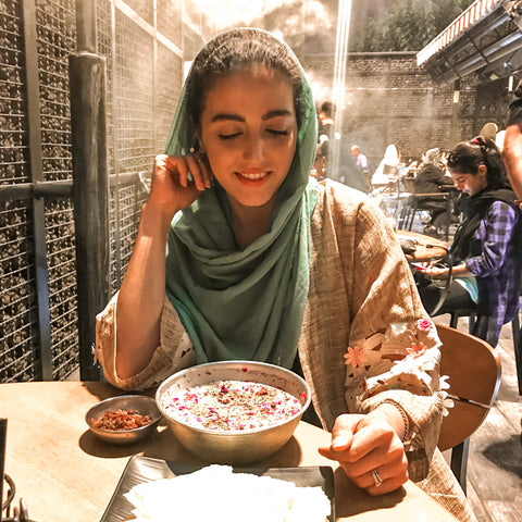 Our founder Sarvin Clark wearing a headscarf pictured in a Persian restaurant about to enjoy authentic Persian food.