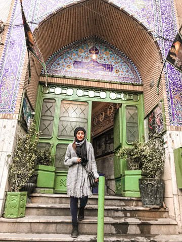 Sarvin pictured in a archway ornately decorated with traditional Persian art.