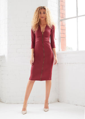 A tight curled blonde female model poses confidently in our Alisha dress. A bodycon burgundy faux leather midi dress.  With a plunging neckline,  3/4 length sleeves and a centre front zip fastening.