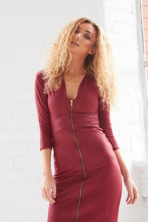 A bodycon burgundy faux leather midi dress. With a plunging neckline,  1/4 length sleeves and a centre front zip fastening.