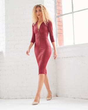 A tight curled blonde model with a slim build takes a step non our Alisha midi dress. A bodycon red faux leather midi dress. With a plunging neckline,  1/4 length sleeves and a centre front zip fastening.