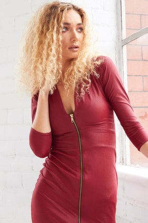 A tight curled blonde model gauzes out of a window in a close up shot of our Alisha dress